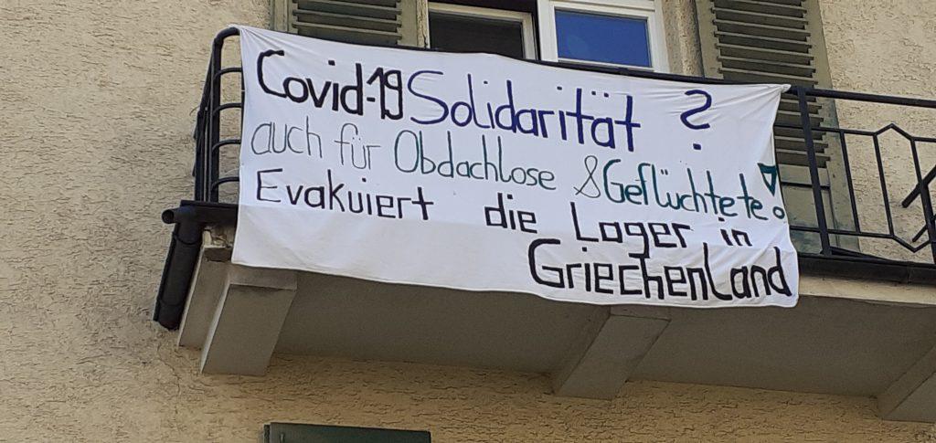 Transpi: Covid-19 Solidarität? Auch für Obdachlose und Geflüchtete! Evakuiert die Lager in Griechenland